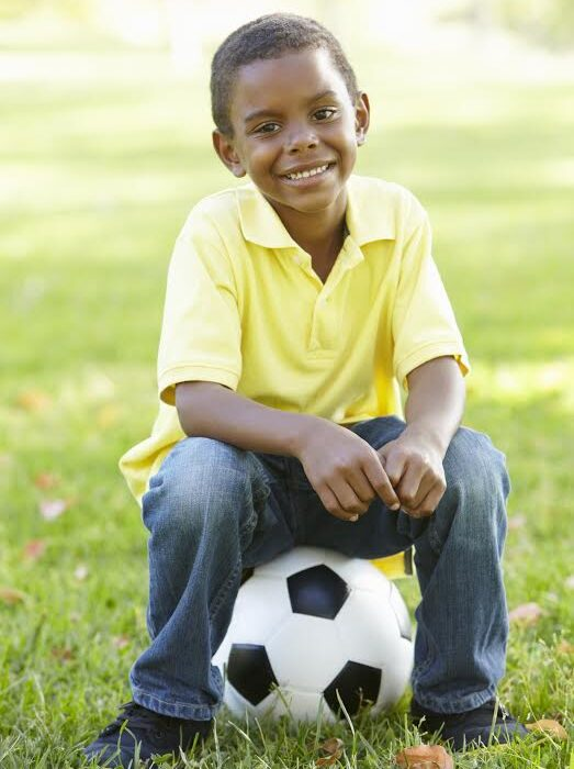 African American Boy Sitting On Football In Park